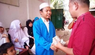 Ustaz Damratua dari Ponpes Al Ikhlas menyerahkan sumbangan santri kepada Ketua Karang Taruna Madina Al Hasan Nasution