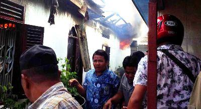 Warga memadamkan api di rumah Hakim Sihombing secara manual