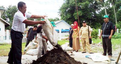 Parno dari KTNA Sumut menuangkan bahan pembuatan pupuk organik di Panyabungan Utara, Rabu (16/12)