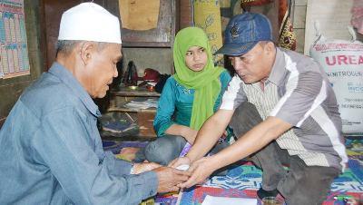 Iskandar Hasibuan dari Gerakan Koin Cinta menyerahkan donasi kepada Zuhdi Nasution kakek Rizky Wasiah di Huraba II, Selasa 2 Pebruari 2016