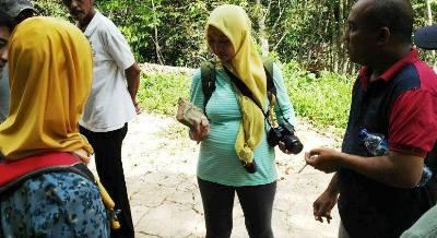 Seorang arkelog wanita dari Balai Arkeologi Medan meneliti material candi di Aek Milas Siabu