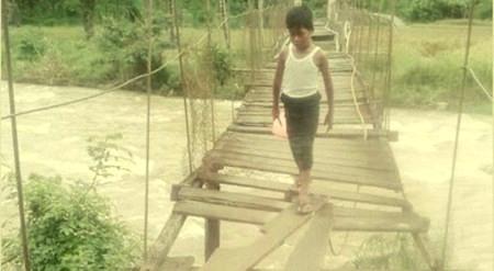 Seorang anak  melintasi rambin yang rusak di Desa Muara Kumpulan, Muara Sipongi