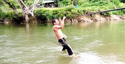 Seorang pria harus bergantung pada seutas tali kawat menyeberang Sungai Batang Gadis  di Desa Muara Siambak Kecamatan Kotanopan.