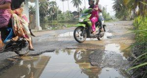 Dua pengendara sepeda motor mengelakkan lobang tergenang di jalur Gunung Manaon-Adian Jior