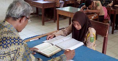 Seorang pelajar SMA Negeri 3 Panyabungan membaca Al-Qur'an di hadapan guru