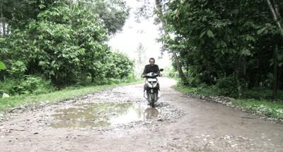 Seorang pengendara sepeda motor melintasi jalan yang rusak di Kecamatan Panyabungan Barat