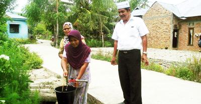 Kepala PDAM Tirta Madina, Nasrin Lubis memantau dua kaum ibu yang mengambil air minum dari jalur pemipaan baru di Desa Gunung Tua Julu.