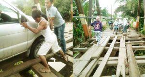 seorang warga memandu supir agar ban mobil tak terperosok di jembatan Desa Air Apa, Sinunukan